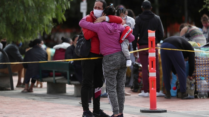 A Venezuelan migrant woman embraces her relative as she prepares to travel to the border via bus, in Bogota, Colombia, Thursday…