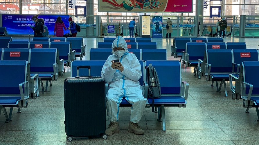 A traveller wearing protective gear to help curb the spread of the coronavirus sits alone on the bench as he waits for his…