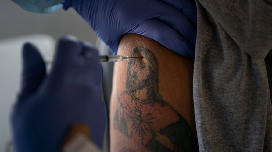 Farm worker Jorge Americano receives the Pfizer-BioNTech COVID-19 vaccine in his arm bearing a tattoo depicting Jesus at Tudor…