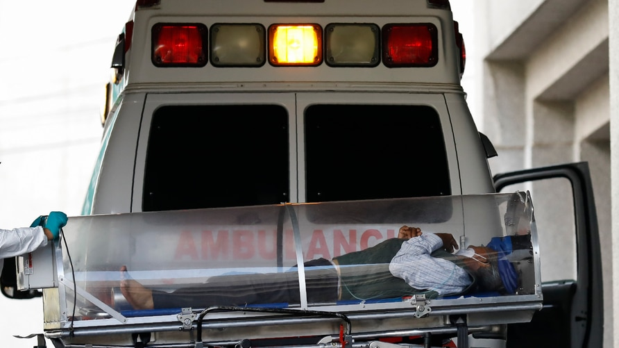 A patient is moved from an ambulance into the COVID-19 treatment center at Dr. Carlos MacGregor Sanchez General Hospital in…