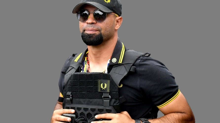 """Henry """"Enrique"""" Tarrio headshot, a Proud Boys leader, graphic element on gray"""