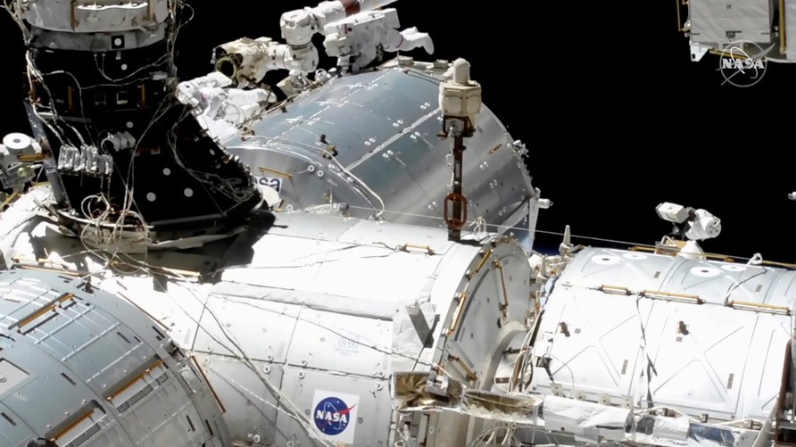 In this image taken from NASA video, NASA astronauts Mike Hopkins, center right, and Victor Glover, center left, work outside…