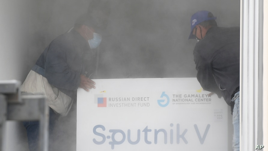 Workers place a box containing doses of the Russian COVID-19 vaccine Sputnik V into a refrigerated container after unloading it…