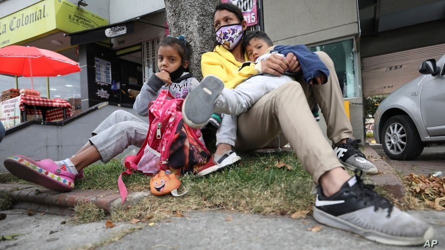 Venezuelan migrant Katerine Valero, 29, and her children Dariusca, 8, left, and Wilkerson, 4, rest outside a strip mall, in…
