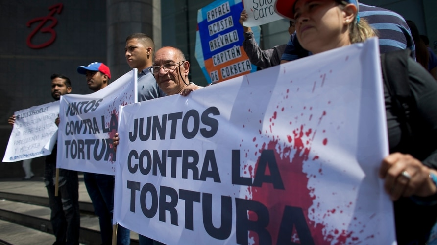 """Opposition activists hold a banner that reads in Spanish """"Together against torture"""" during a protest outside the United Nations…"""