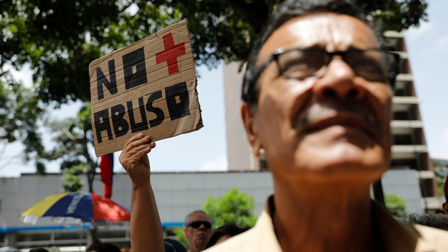 """A woman holds up a sign that reads in Spanish """"No moro abuse"""" during a protest against the government of President Nicolas…"""