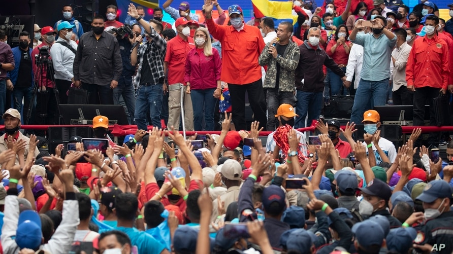 Venezuela's President Nicolas Maduro, center, and first lady Cilia Flores who is also a candidate for the National Assembly,…