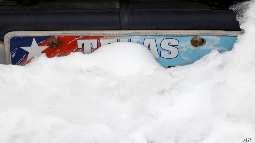 Snow begins to melt on a car in Euless, Texas, Thursday, Feb. 18, 2021. (AP Photo/Michael Ainsworth)