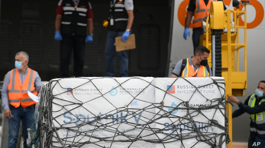 Workers unload a shipment of the Russian COVID-19 vaccine Sputnik V, at the Simon Bolivar International Airport in Maiquetia,…
