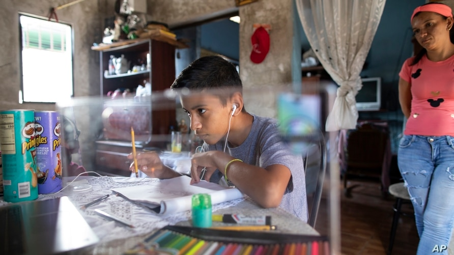 Samuel Andres Mendoza looks at a picture of a Pokemon on his computer before drawing it, at his home in Barquisimeto, Venezuela…