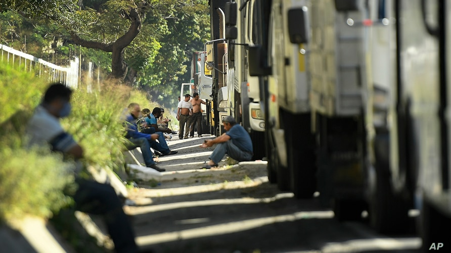 Truck drivers wait next to their trucks to fill up their tanks with diesel during a fuel shortage in Caracas, Venezuela,…