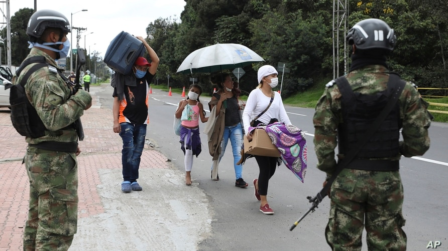 Under the watch of Colombian soldiers, Venezuelan migrants leave on foot toward the Venezuelan border after a lockdown ordered…