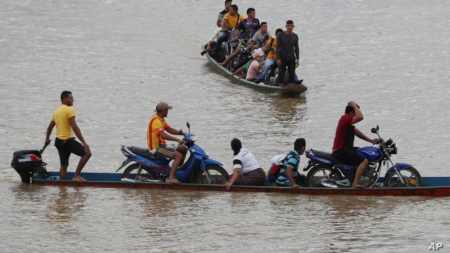 Venezuelans cross the Arauca River, the natural border between Venezuela and Colombia, to take shelter in Arauquita, Colombia,…