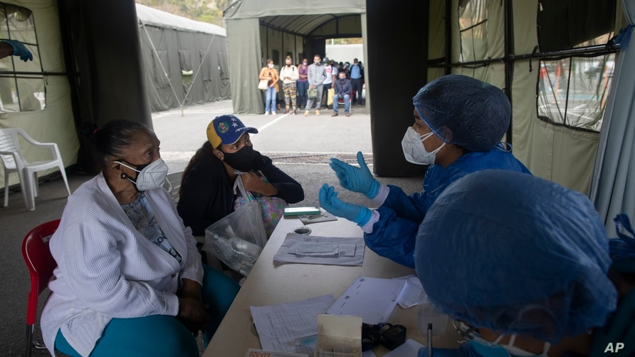 Women listen to a health worker as they are screened for COVID-19 at a field hospital set up on the parking lot of the Poliedro…