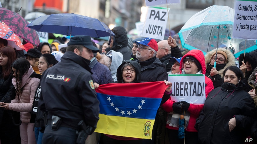 A woman holds a Venezuelan flag as others pack the Puerta del Sol square waiting for Juan Guaido during his visit to Madrid,…