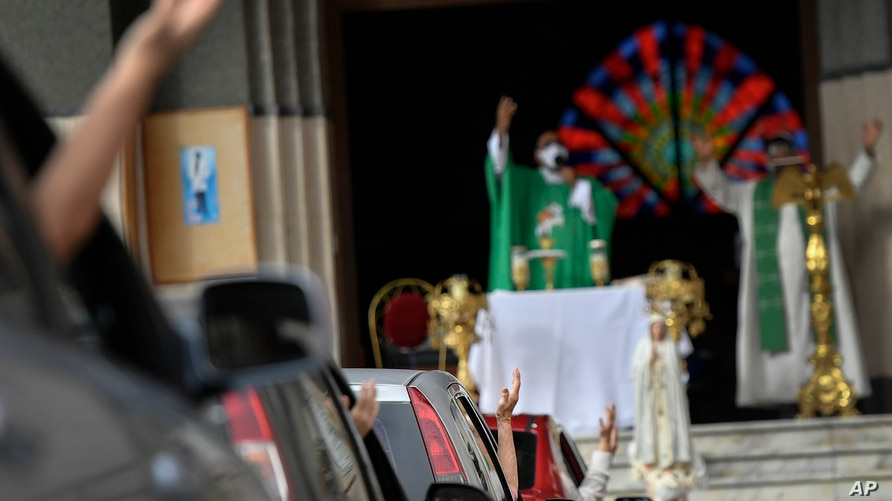 Parishioners attend a drive-in Sunday Mass set up by Father Jonathan Gonzalez to circumvent the regulations that prevent…