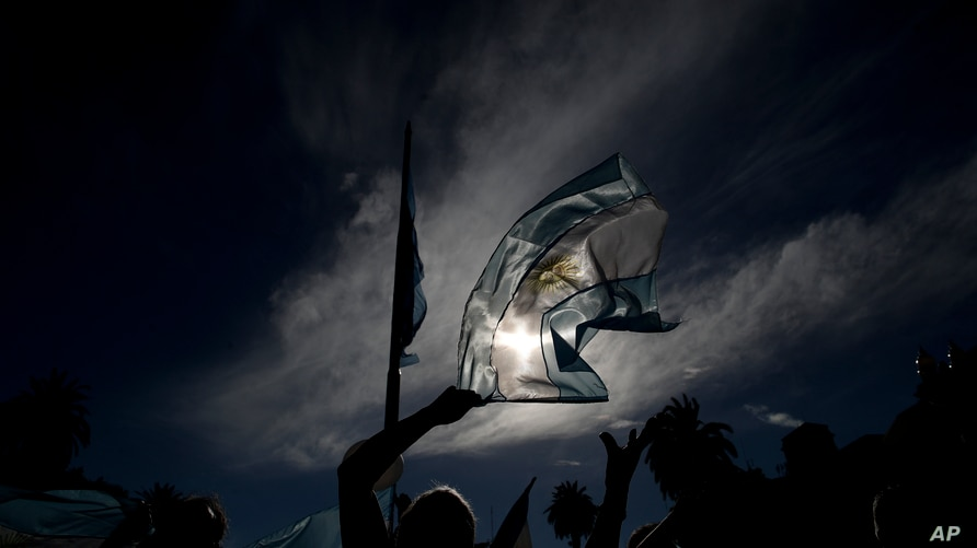 A demonstrator waves a national flag during a protest against the government of President Alberto Fernandez and its handling of…