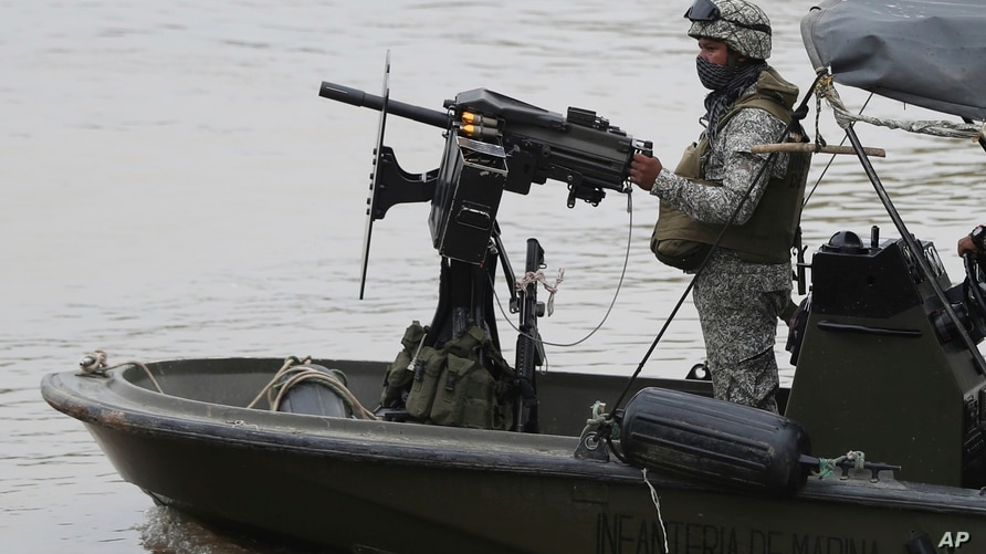 Colombian navy soldiers patrol the Arauca River, the natural border with Venezuela, seen from Arauquita, Colombia, Friday,…