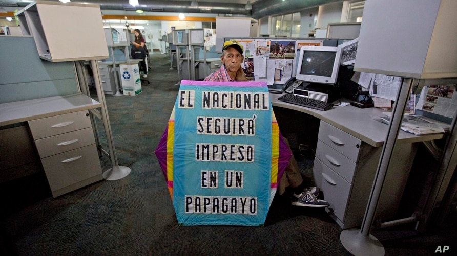 """A man holds a kite with a message that reads in Spanish: """"El Nacional will always publish even if it has to be on a kite"""" in…"""