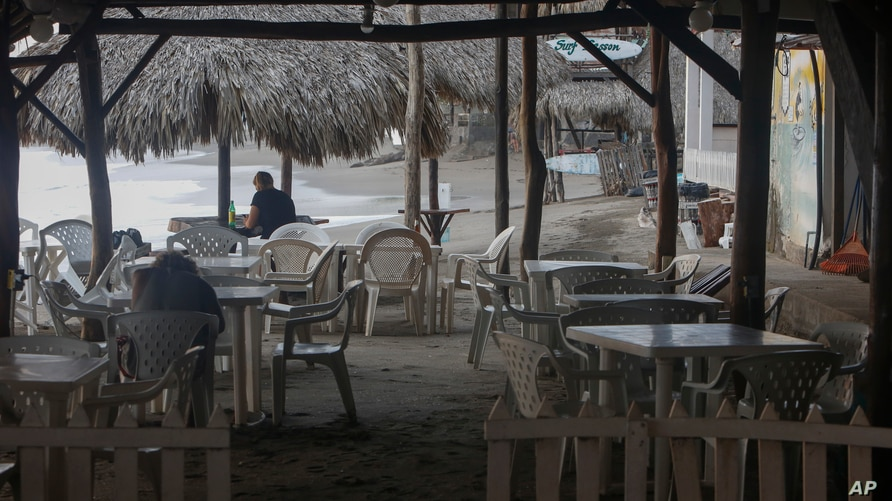 A few visitors visit a beachside restaurant in the coastal town of Las Peñitas, Nicaragua, Tuesday, Sept. 11, 2018. Economists…