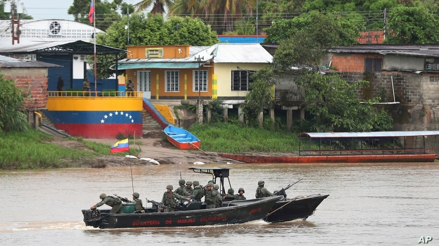 Venezuelan navy soldiers patrol the Arauca River, the natural border with Colombia, seen from Arauquita, Colombia, Friday,…