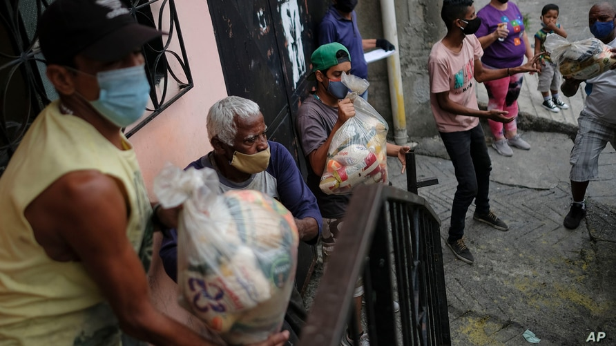 Residents help to unload bags of basic food staples, such as pasta, sugar, flour and kitchen oil, provided by a government food…
