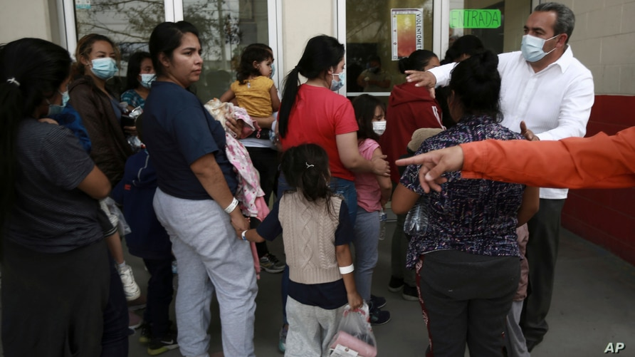 Volunteers receive a group of Central America's migrants after they were deported from the United States, at a sports complex…