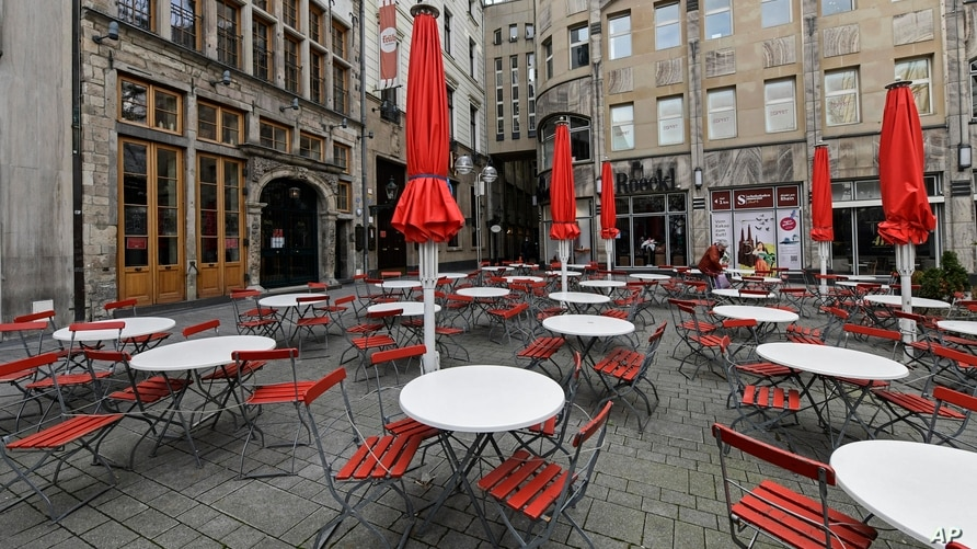FILE - In this March 18, 2021 file photo, empty tables are seen on a deserted square in normally very busy old town of Cologne,…