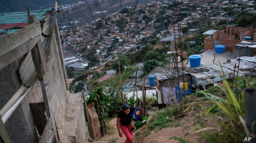 A woman with her son climb up the hill in the El Quilombo neighborhood of Caracas, Venezuela, Saturday, Feb. 13, 2021, amid the…
