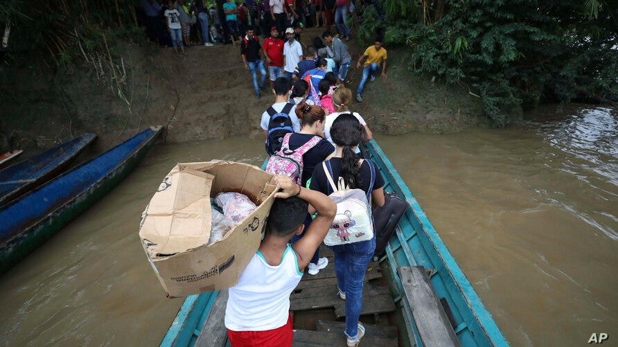 Venezuelans disembark a boat on the Arauca River, the natural border between Venezuela and Colombia, as they arrive to…