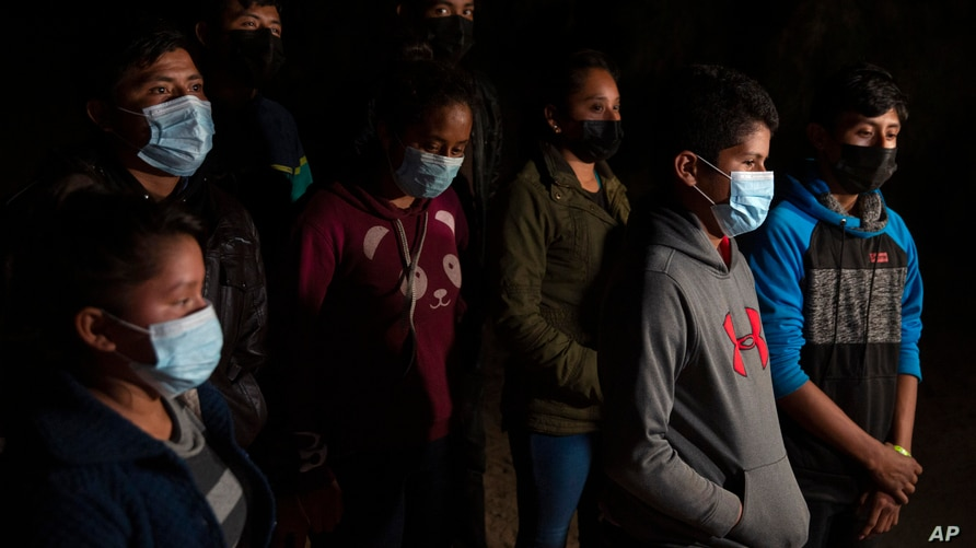 FILE - In this Tuesday, March 30, 2021 file photo, migrants from Central American countries wait to be taken to a Border Patrol…