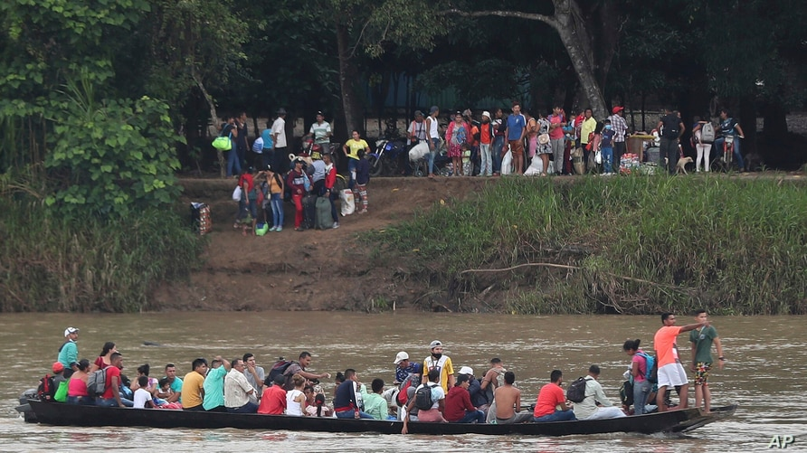 Venezuelans cross the Arauca River, the natural border between Venezuela and Colombia, to travel to Arauquita, Colombia, Friday…