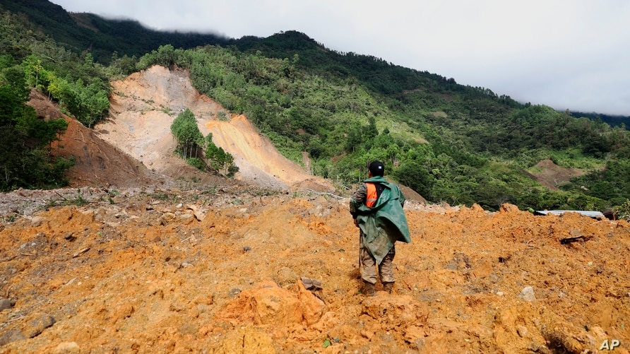 A member of a search and rescue team looks for survivors through the destruction caused by a massive, rain-fueled landslide in…