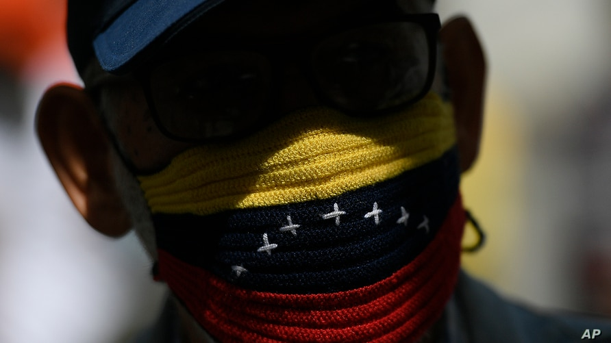A protester, wearing a handwoven protective face mask with the colors representative of the Venezuelan national flag, attends a…