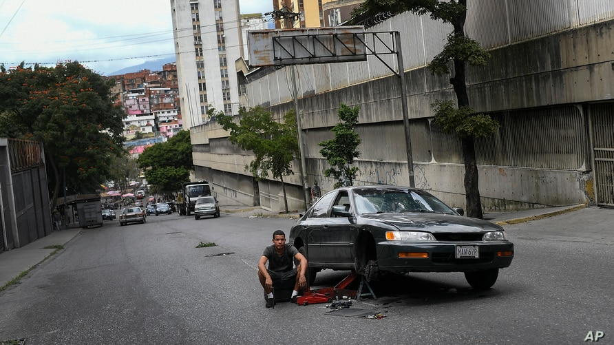 A man sits in the middle of the road alongside his broken down car in the Petare neighborhood of Caracas, Venezuela, Saturday,…