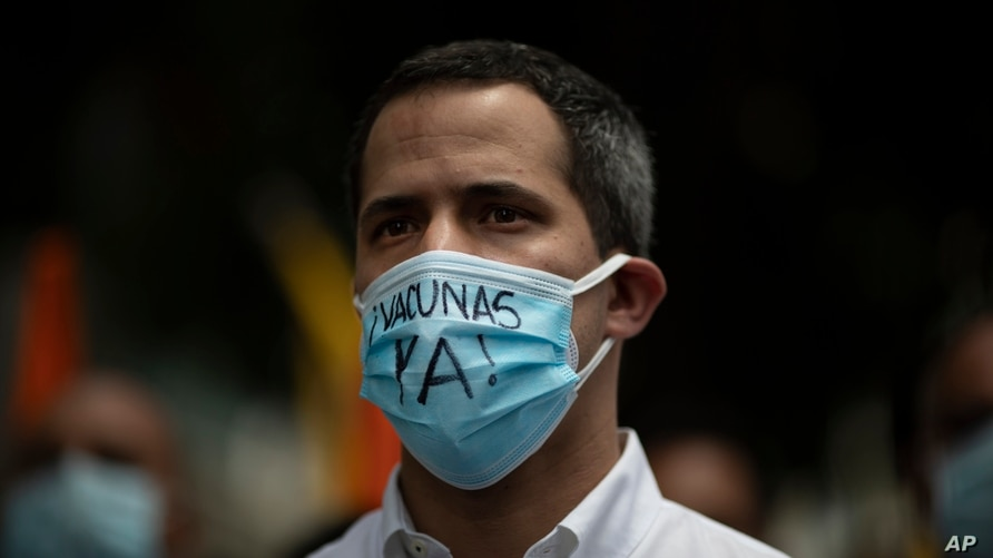 """Venezuelan opposition leader Juan Guaido, wearing a protective face mask with a message that reads in Spanish: """"Vaccines now!"""",…"""