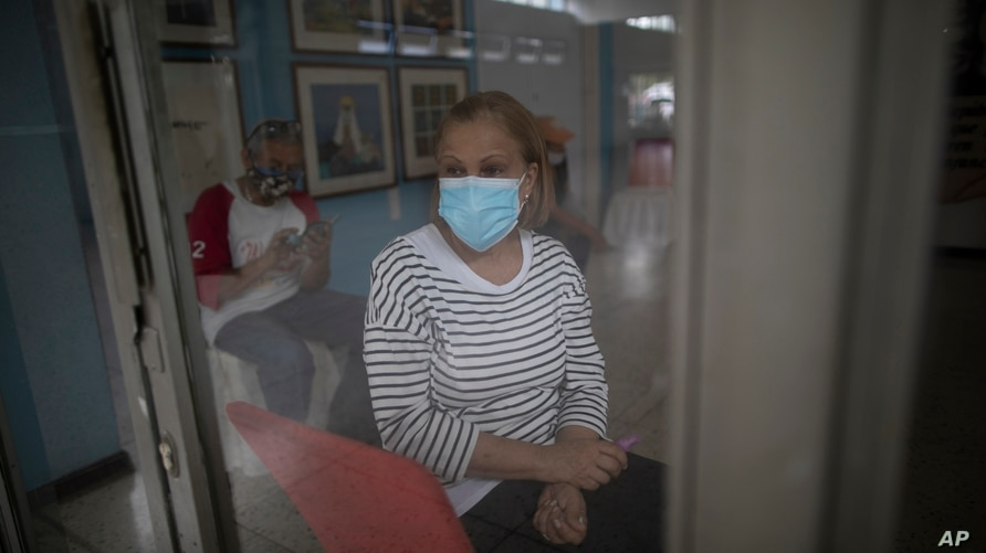 Maritza Diaz, 63, waits to be inoculated with a dose of the Sputnik V COVID-19 vaccine at the Perez Carreno public hospital in…