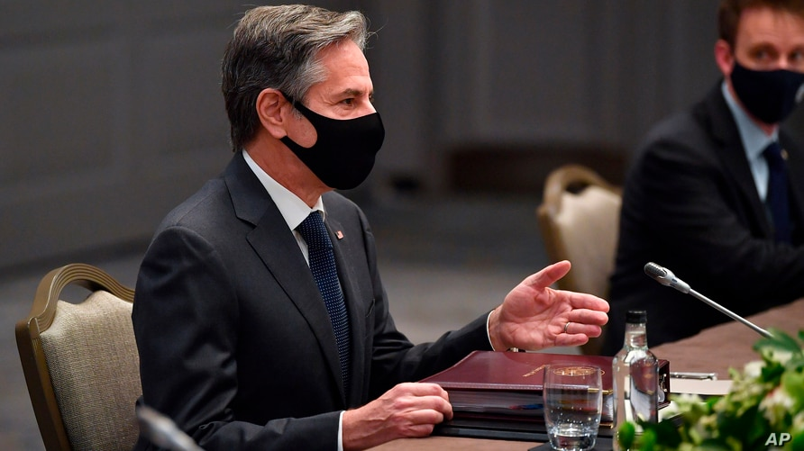 United States Secretary of State Antony Blinken, wearing a face mask to curb the spread of COVID-19, sits at a table for during…