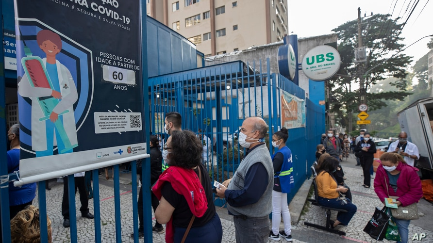 People wait in line outside a community medical center to get a shot of the Pfizer COVID-19 vaccine in Sao Paulo, Brazil,…