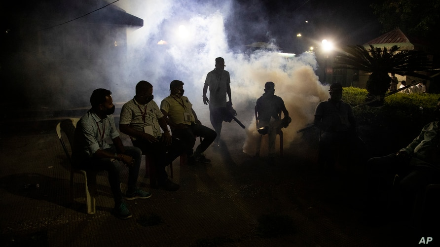 A municipal worker fumigates as supporters of Bharatiya Janata Party wait outside a vote counting center in Gauhati, India,…