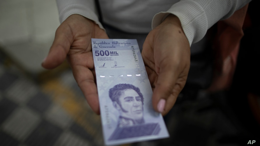 A woman shows a new 500,000 Bolivar bill after withdrawing it from a bank in Caracas, Venezuela, Tuesday, March 16, 2021. The…