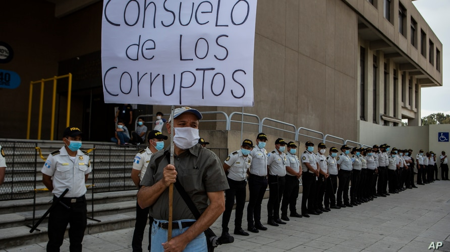 """A man holds a poster with a message that reads in Spanish: """"Consuelo is one of the corrupt,"""" during a protest demanding the…"""