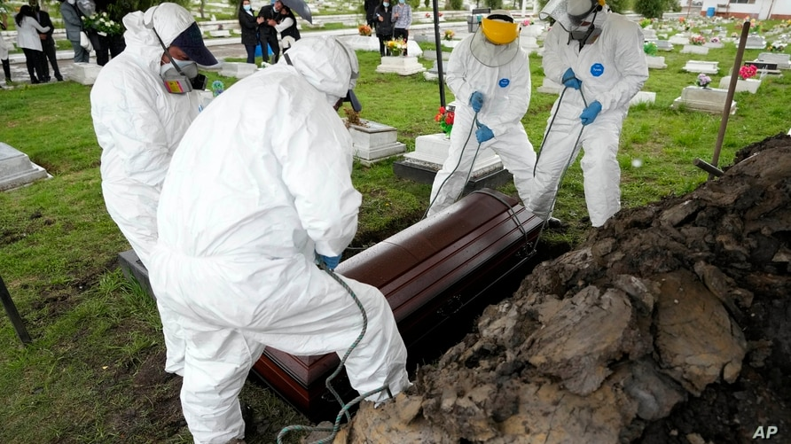 Cemetery and funeral workers lift a coffin containing the remains of a man who died of COVID-19, at the Zipaquira's Park…