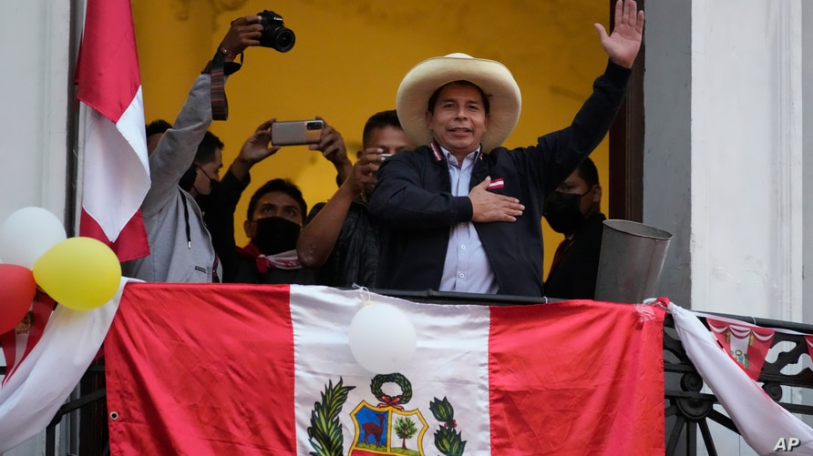 Presidential candidate Pedro Castillo waves to supporters celebrating partial election results that show him leading over Keiko…