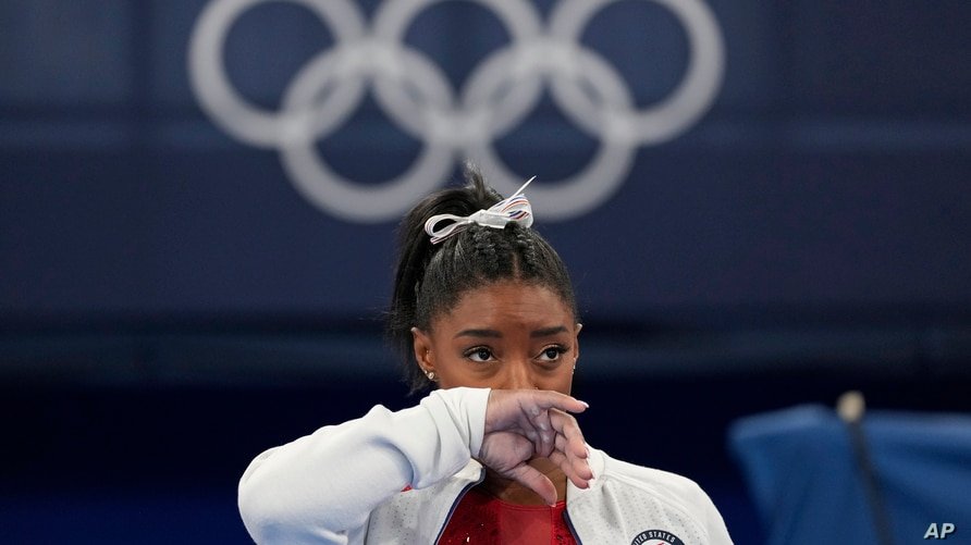Simone Biles, of the United States, watches gymnasts perform after an apparent injury, at the 2020 Summer Olympics, Tuesday,…