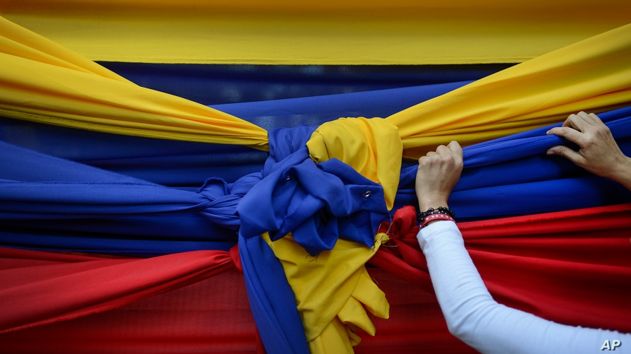 An opposition supporter holds fabric featuring the colors of the Venezuelan flag before a rally with opposition leader Juan…