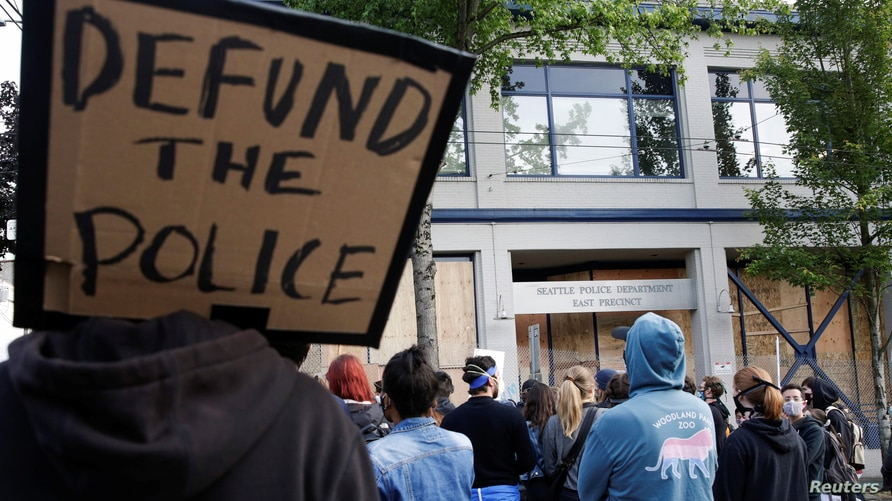 "A protester holds a sing that reads ""defund the police"" after Seattle Police vacated the department's East Precinct in Seattle"