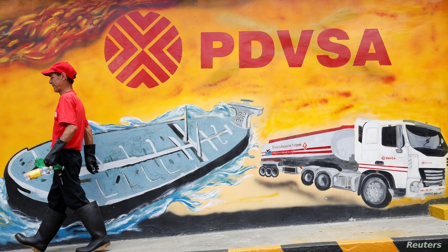 FILE PHOTO: A worker walks past a mural with a PDVSA logo at its gas station in Caracas