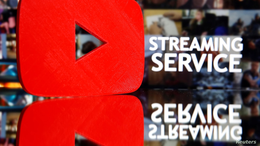 "FILE PHOTO: A 3D-printed Youtube logo is seen in front of displayed ""Streaming service"" words in this illustration"