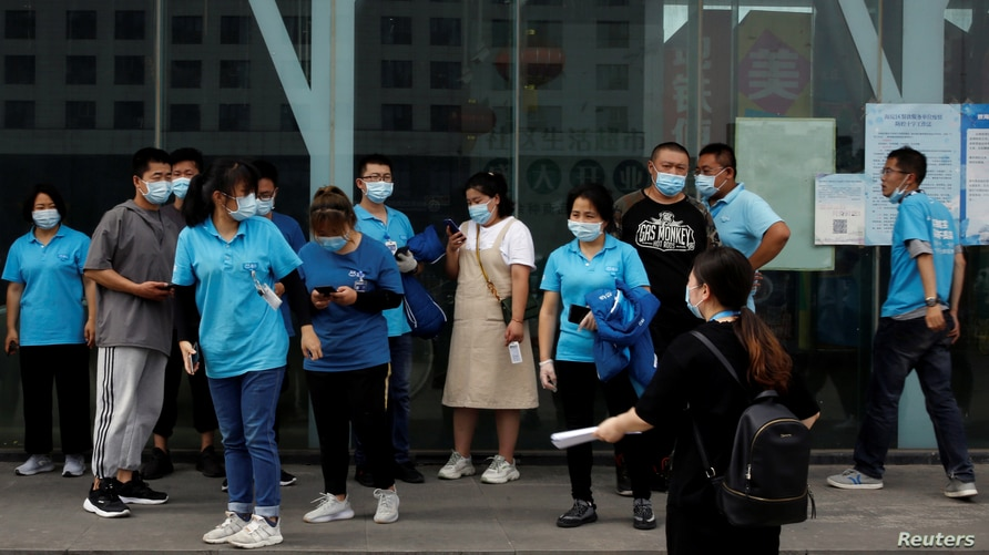 People wait outside a site for nucleic acid tests in Beijing